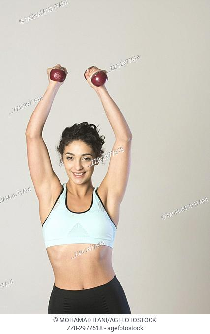Beautiful young woman exercising with dumbbells