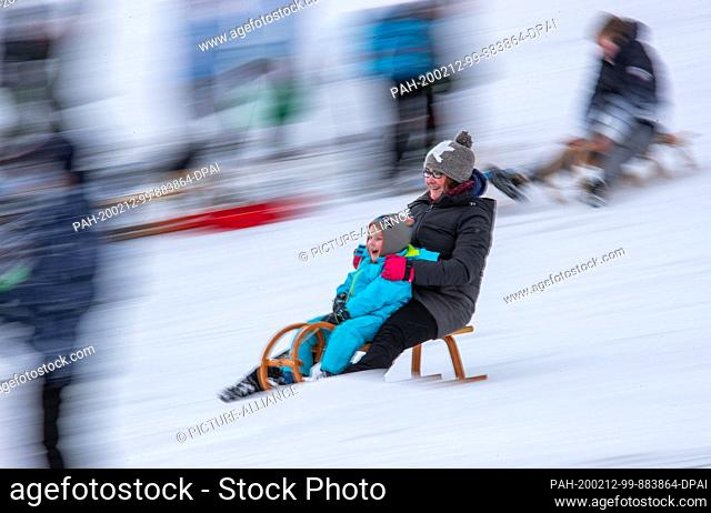 12 February 2020, Saxony, Altenberg: Raphael obviously has fun sledging with his mother Claudia in partly sunny weather. A thin layer of snow attracts...