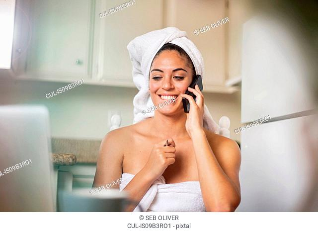 Young woman wrapped in towels looking at laptop and having smartphone call at kitchen table