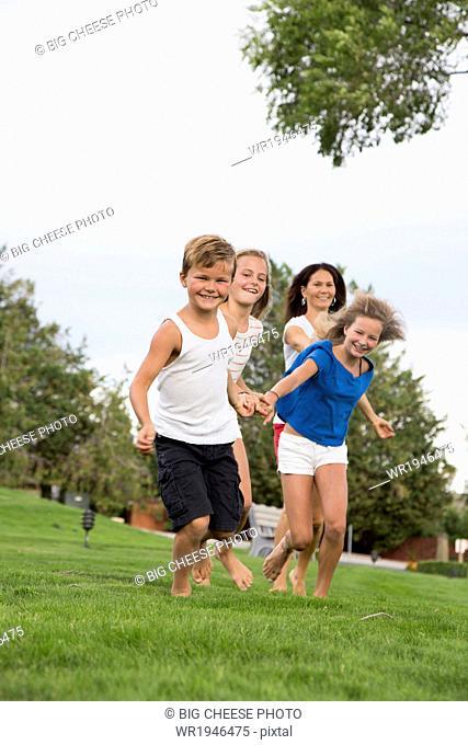 Mother running on grass with her three children