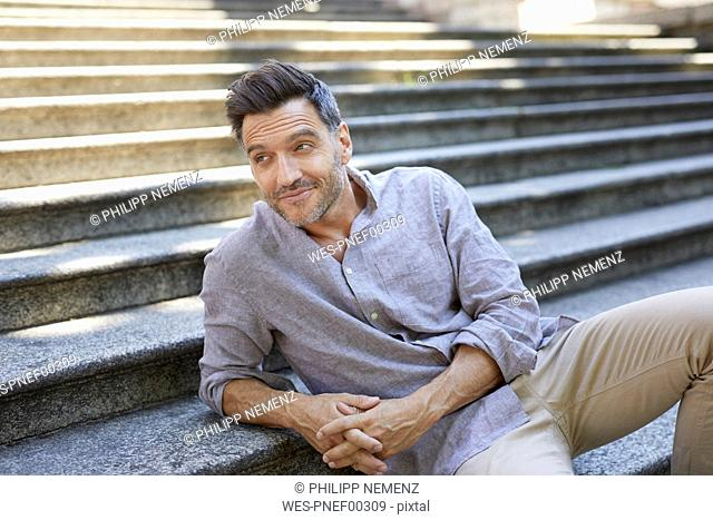 Portrait of smiling mature man sitting on stairs