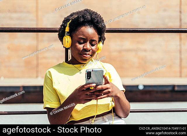 Portrait of black girl with afro hair and hoop earrings listening to music with her cell phone and yellow headphones in an urban space in the city