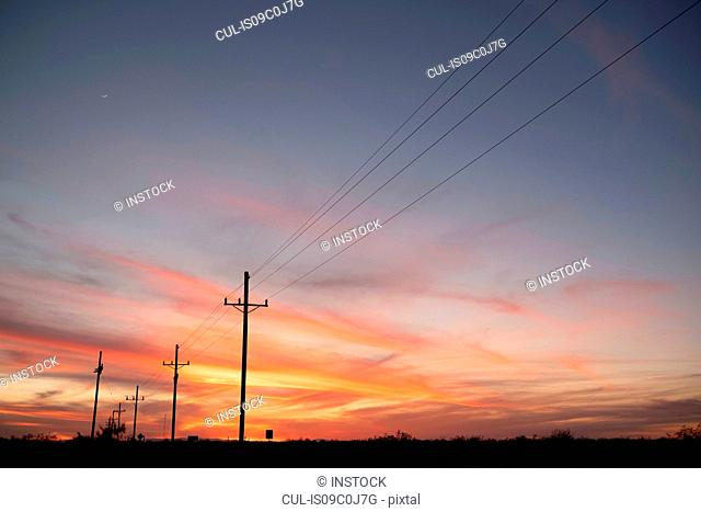 Sunset over highway lined with telephone poles