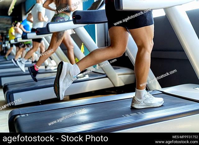Male and female athletes running on treadmill in gym