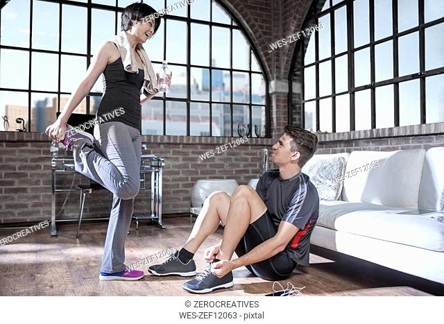Young man and woman preparing in exercise room