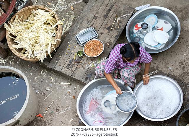 a women clean the dishes at a restaurant at the u bein bridge in Amarapura near the City of Mandalay in Myanmar in Southeastasia