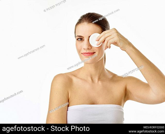 Portrait of smiling woman covering eye with cotton pad