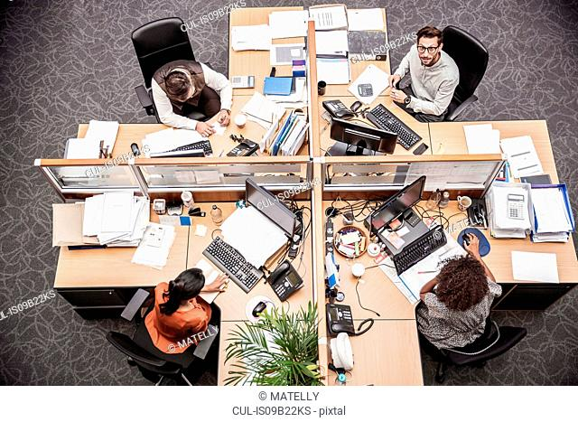 Overhead view of businessmen and women at office desk