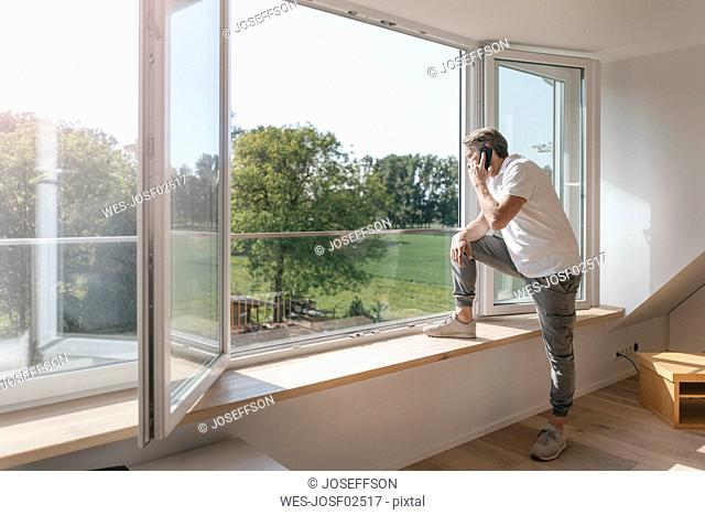 Mature man on the phone at the window in empty room