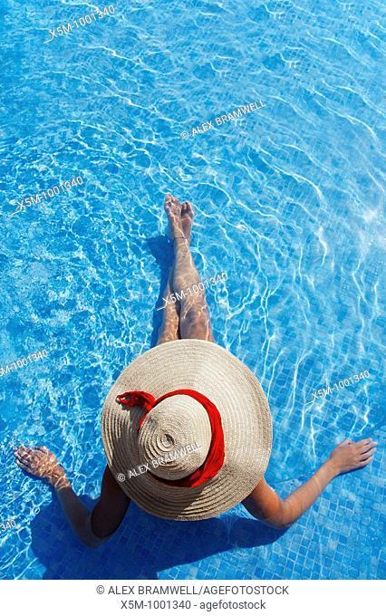 Woman in a sun hat sunbathing in a blue swimming pool