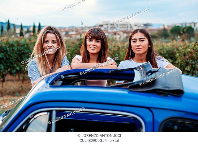 Friends posing beside car in countryside, Florence, Toscana, Italy