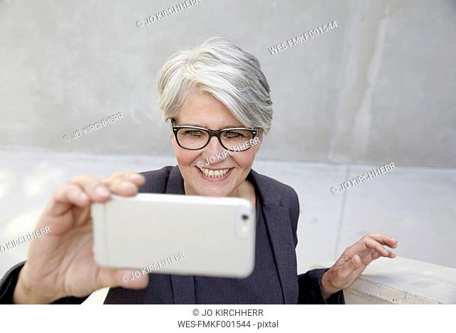Portrait of smiling career woman taking a selfie with smartphone