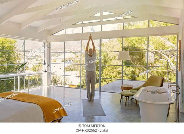Mature man practicing yoga with hands clasped overhead in luxury bedroom