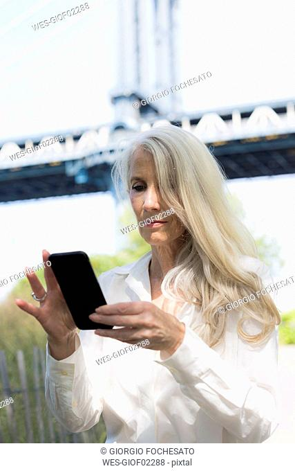 USA, Brooklyn, mature woman using cell phone in front of Manhattan Bridge