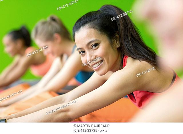 Portrait smiling woman stretching in forward fold pose in gym studio