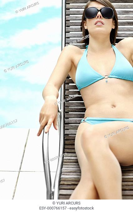 Sensual young bikini model relaxing on the recliner by the swimming pool