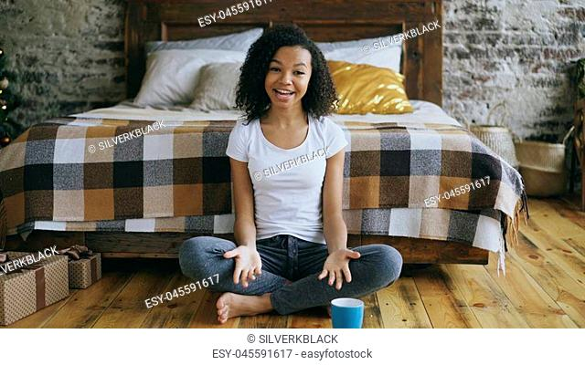 Attractive mixed race girl teenager sitting near bed recording video blog looking into camera and talking to her followers at home