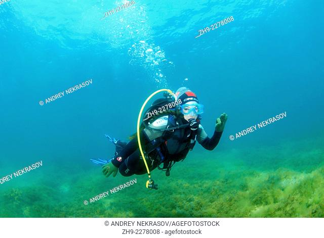 """young woman with pigtails swimming underwater and shows sign """"""""OK"""""""". Black Sea, Crimea, Ukraine, Eastern Europe"""