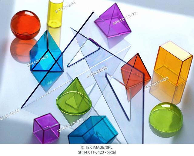 Geometric shapes used in maths and calculus education sitting on drawing equipment