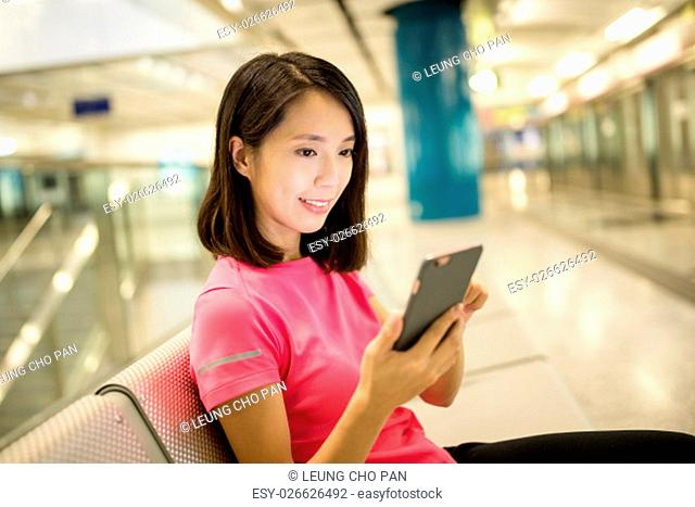 Woman using smart phone in train station