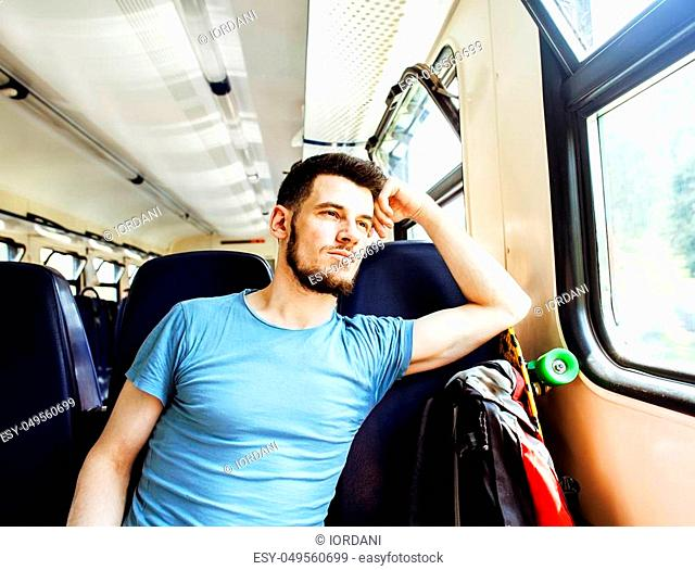 young pretty modern hipster guy traveller on train with skateboard alone, lifestyle vacation people concept close up smiling cool in window