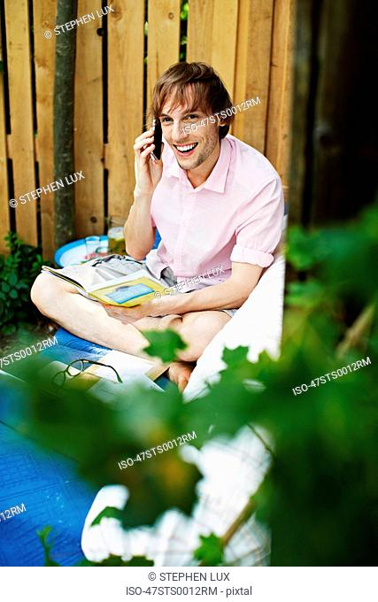 Man using laptop on sofa outdoors