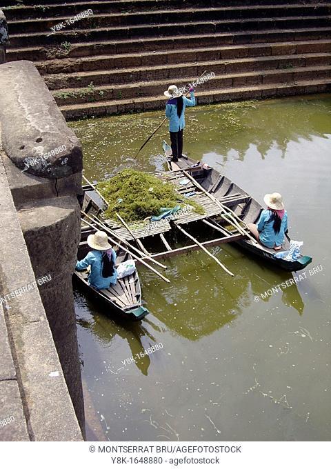 Three female lake bottom cleaners on boat at Angkor Wat, Cambodia