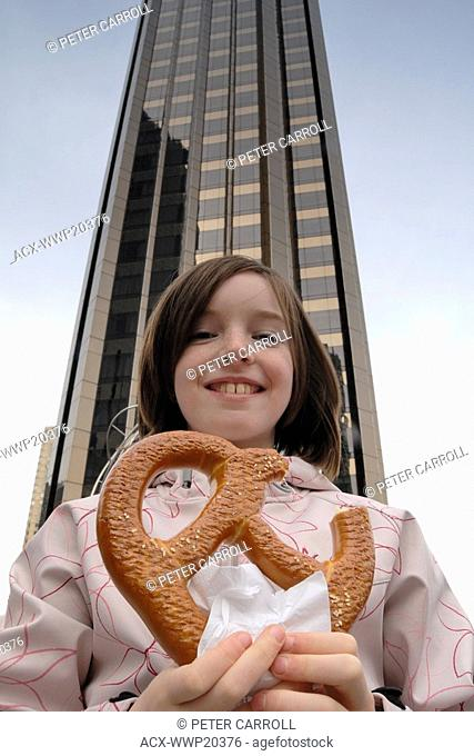 Young girl age 10 holding a soft pretzel a popular New York street vendor treat at Columbus Circle in front of Trump International Tower - New York City, NY