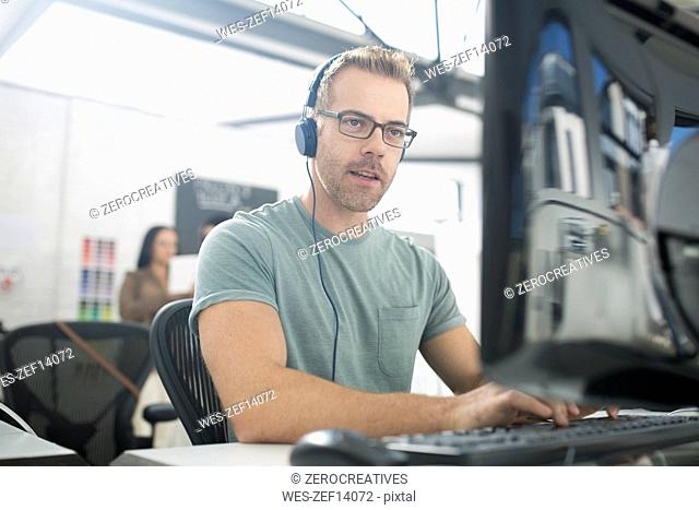 Employee wearing headphones at desk