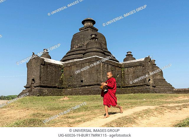 Novice Buddhist monk collects morning alms in front of Laymyetnha, Lemyethna Temple in Mrauk U, Burma, Myanmar
