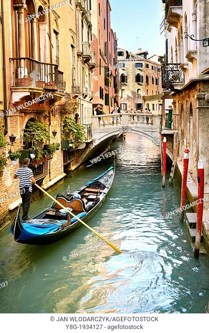 Venice - gondolier with his gondola in one of the narrow canals of Venice, Italy, UNESCO