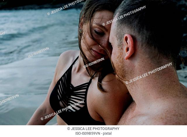 Couple at beach, looking lovingly at each other, Saint Martin, Caribbean