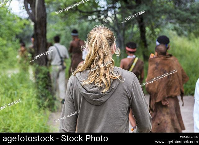 Tourists on a walking trail with members of the San people, bushmen in Botswana