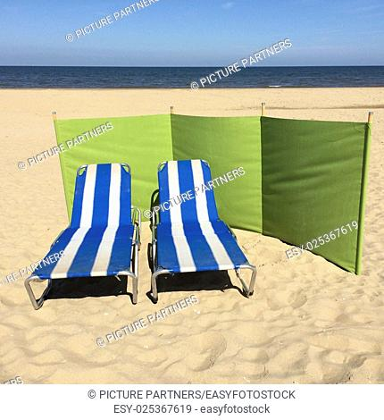 Two empty striped beach chairs on the beach