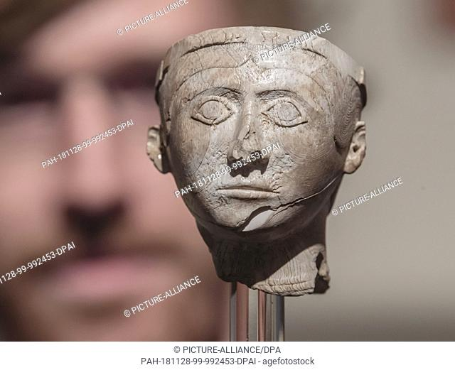26 November 2018, Baden-Wuerttemberg, Karlsruhe: A person in the Badisches Landesmuseum in Karlsruhe Castle looks at a replica of a man's head from Mycenae