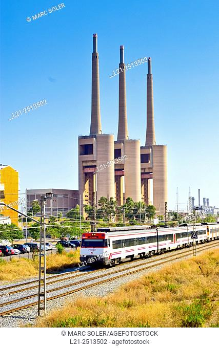 Renfe train running on the tracks. Thermal power station, electric power plant, Fecsa-Endesa. Sant Adrià del Besòs, Barcelona province, Catalonia, Spain