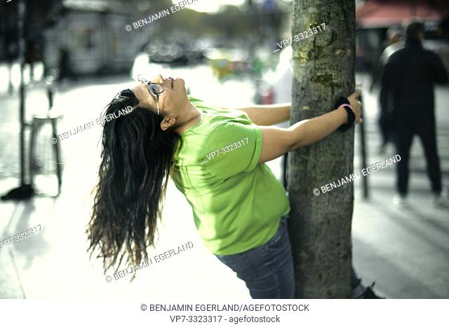 eased woman embracing tree in city, in Paris, France