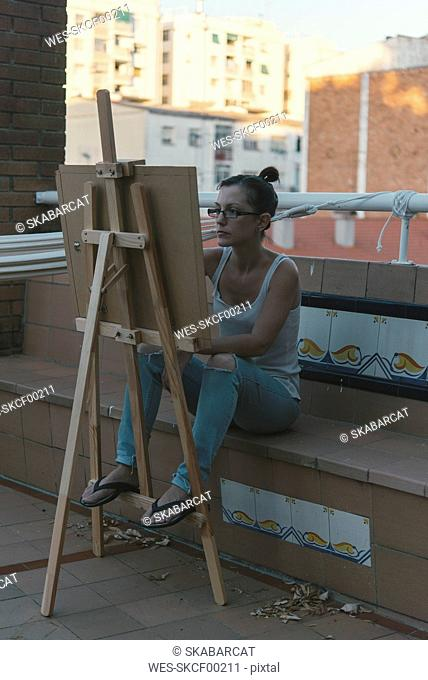 Young woman drawing on roof terrace of her penthouse