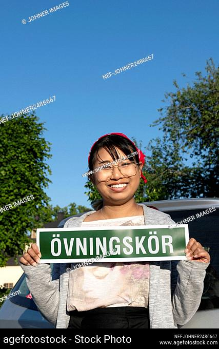 Female student driver holding sign