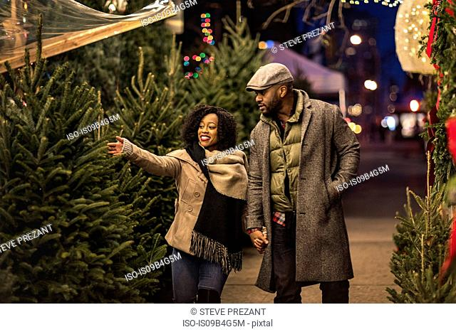 Couple selecting Christmas tree at Christmas market at night, New York, USA