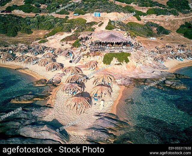 Man in bar on a beautiful beach aerial view drone shot, Sithonia, Greece
