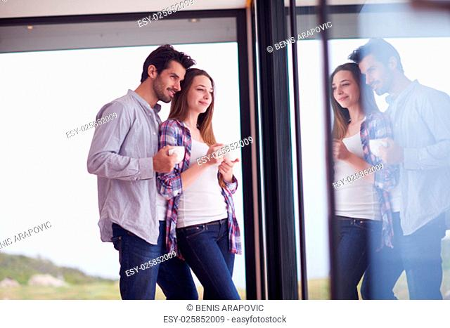 relaxet young couple drink first morning coffee over big bright window in moder home villa interior
