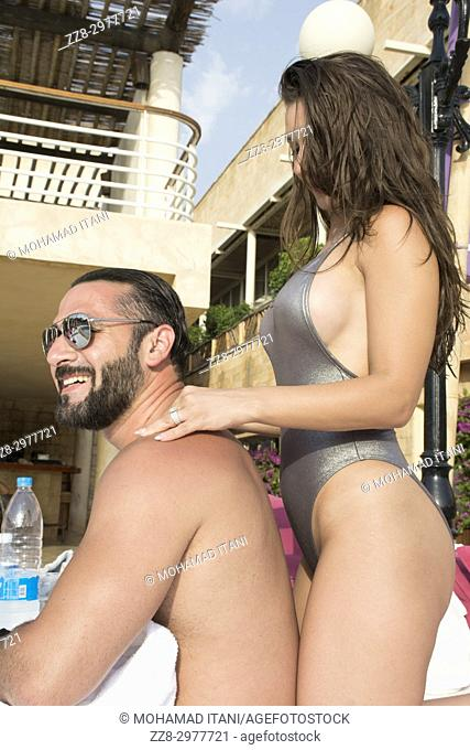 Young woman in bikini giving a massage to her boyfriend by the pool