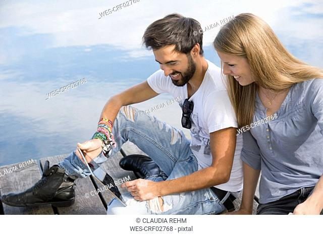 Smiling young couple sitting on jetty at a lake with tablet