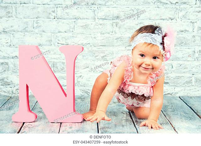 Beautiful and cute girl in pink dress with the letter N. Emotional girl