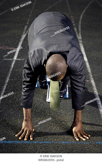 Businessman in starting position ready to race