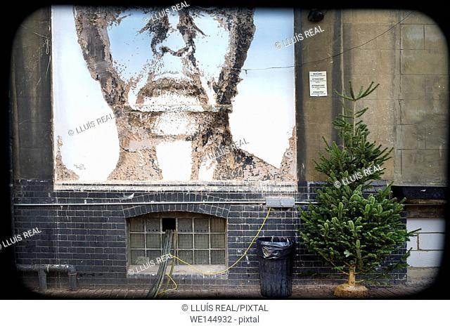 Street Art of a man face on a wall with a Christmas tree behind, on the Dray Walk street near Brick Lane, East London, London, England, UK