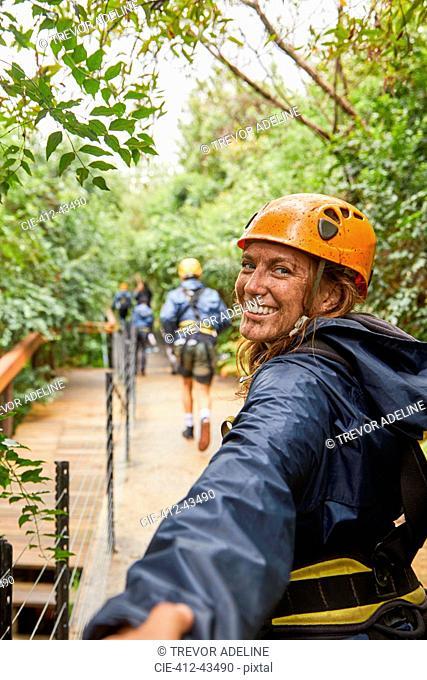 Portrait happy, muddy woman enjoying zip lining