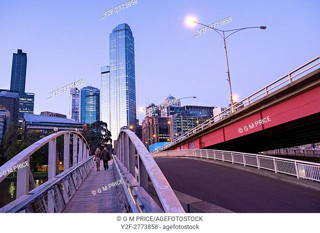 couple walking on pedestrian bridge and Kings Bridge, with Melbourne city skyline