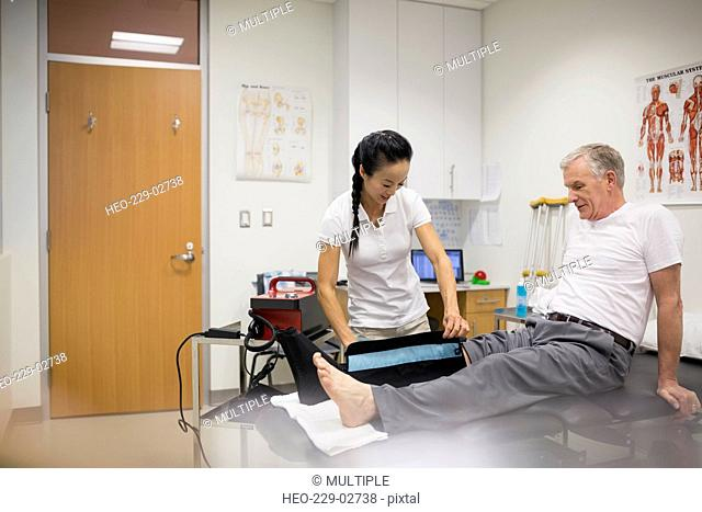 Physical therapist using compression knee wrap on patient